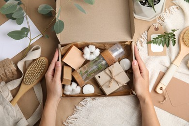 Woman with eco friendly personal care products at brown table, top view