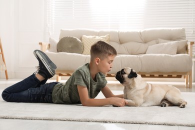Boy with his cute pug lying on floor in living room