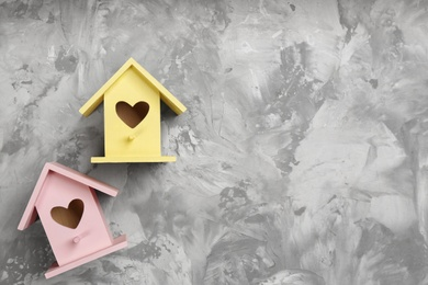 Beautiful bird houses with heart shaped holes on light grey background, flat lay. Space for text