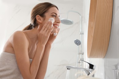 Young woman applying cleansing foam onto her face in bathroom