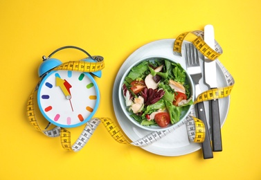 Plate of tasty salad, alarm clock and measuring tape on yellow background, flat lay. Nutrition regime