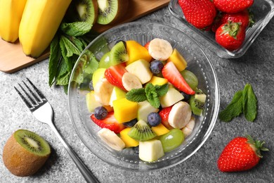 Delicious fresh fruit salad in bowl on grey table, flat lay
