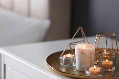 Beautiful burning candles and decor on table at home. Space for text