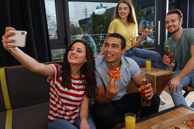 Happy young people with delicious pizza taking selfie in cafe