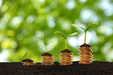 Stacked coins and green seedlings on ground outdoors, bokeh effect. Investment concept