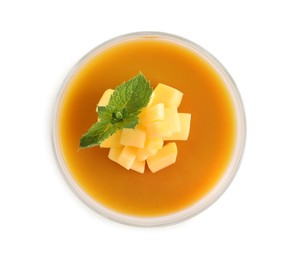 Delicious mango coulis with fresh fruit pieces and mint isolated on white