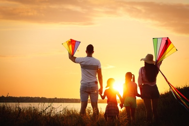 Parents and their children playing with kites outdoors at sunset, back view. Spending time in nature