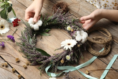 Florist making beautiful autumnal wreath with heather flowers at wooden table, closeup