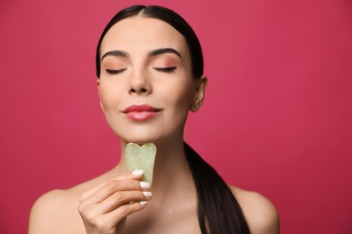 Beautiful young woman doing facial massage with gua sha tool on pink background
