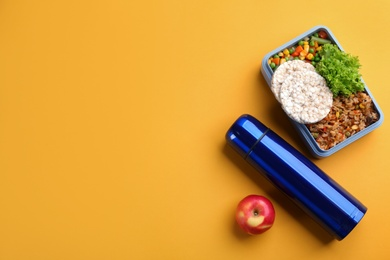 Thermos, lunch box and apple on orange background, flat lay. Space for text