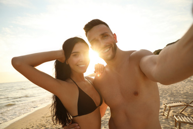 Happy young couple taking selfie on beach at sunset