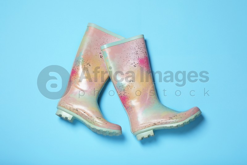 Pair of rubber boots on light blue background, top view