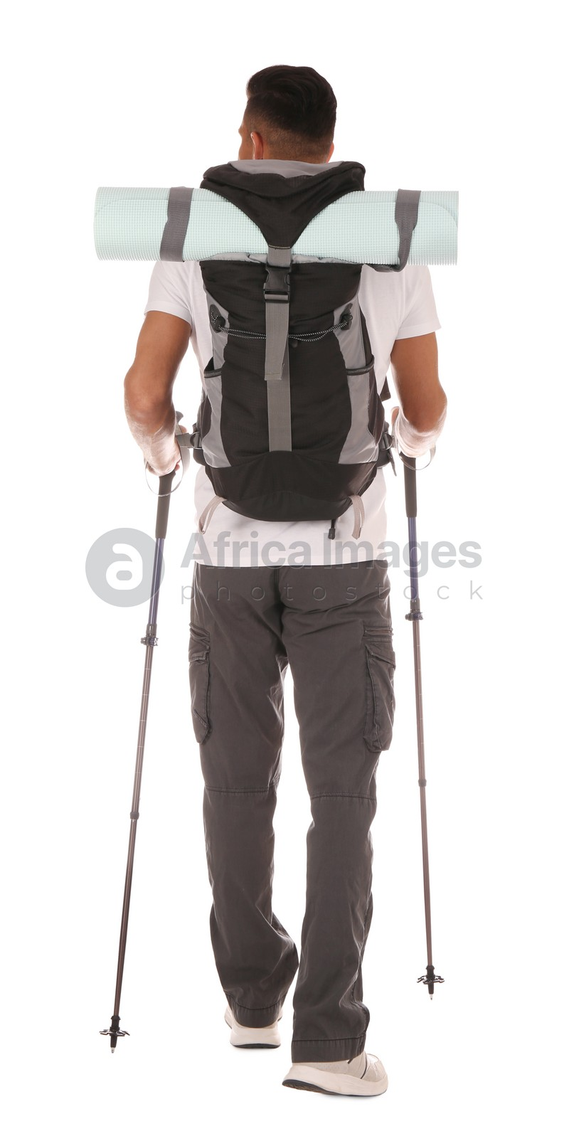 Male hiker with backpack and trekking poles on white background, back view