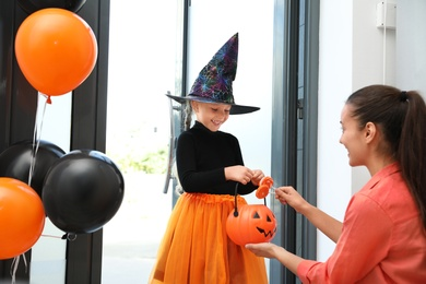 Cute little girl dressed as witch trick-or-treating at doorway. Halloween tradition