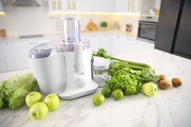 Modern juicer, fresh vegetables and fruits on table in kitchen