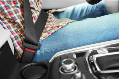 Person with fastened safety belt in car, closeup