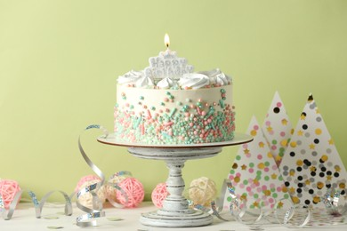 Delicious birthday cake and party decor on white wooden table against light background