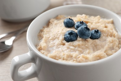 Tasty oatmeal porridge with blueberries in bowl on table, closeup