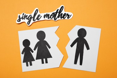 Being single mother after divorce concept. Paper cutouts demonstrating broken family on orange background, flat lay