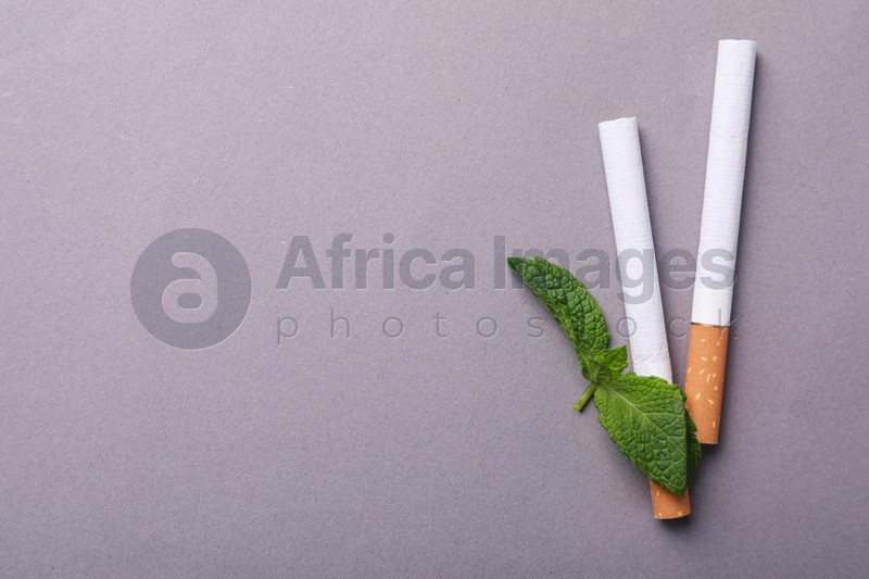 Menthol cigarettes and mint leaves on grey background, flat lay. Space for text