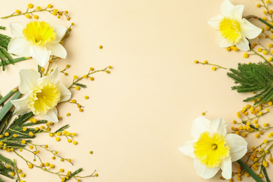 Flat lay composition with spring flowers on beige background, space for text