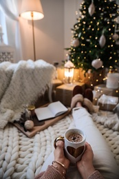 Woman with cup of cocoa in room decorated for Christmas, closeup