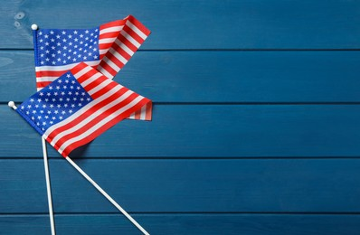 American flags on blue wooden table, flat lay with space for text. Memorial Day