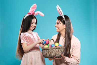 Mother and daughter in bunny ears headbands with basket of Easter eggs on color background