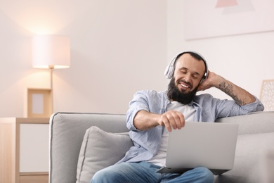 Mature man with headphones and laptop on sofa at home