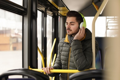 Young man listening to music with headphones in public transport