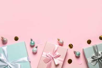 Beautiful gift boxes, Christmas balls and confetti on pink background, flat lay. Space for text