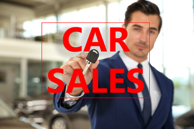 Salesman with key in car dealership, focus on hand