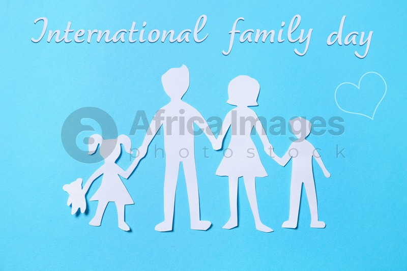 Paper figures of parents and their children on light blue background, top view. Happy Family Day