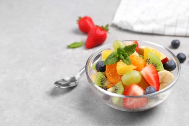 Delicious fresh fruit salad in bowl on light table, space for text
