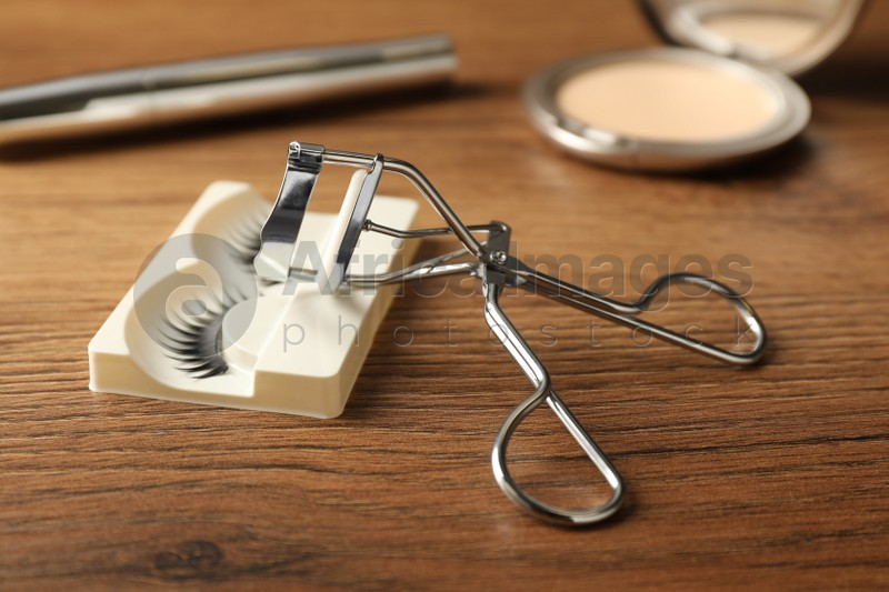 False eyelashes and curler on wooden table, closeup