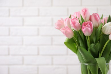 Beautiful bouquet of tulips in glass vase against white brick wall. Space for text