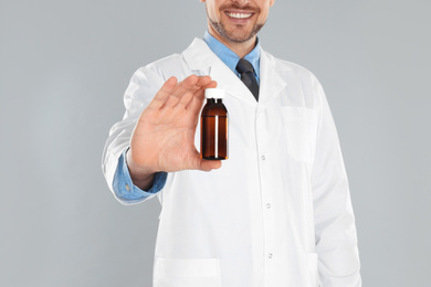 Professional pharmacist with syrup on light grey background, closeup