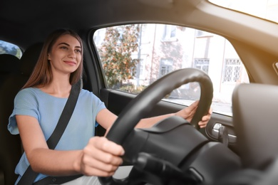 Young woman with fastened safety belt on driver's seat in car