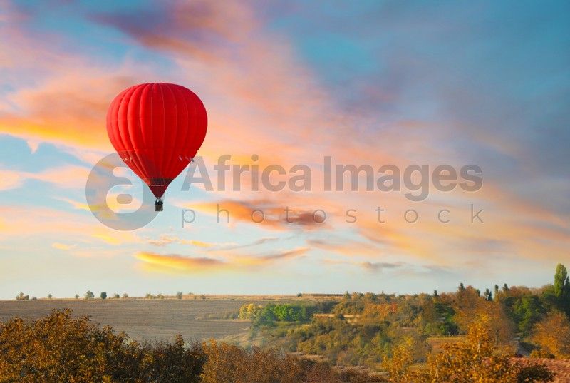 Colorful hot air balloon flying over countryside. Space for text
