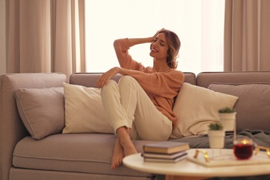 Beautiful young woman relaxing at home. Cozy atmosphere