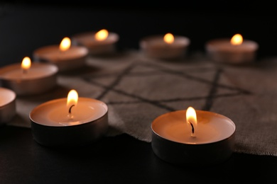 Fabric with star of David and burning candles on black background, closeup. Holocaust memory day
