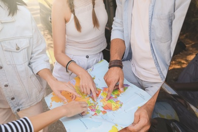 Group of friends with map near car outdoors, closeup. Summer trip