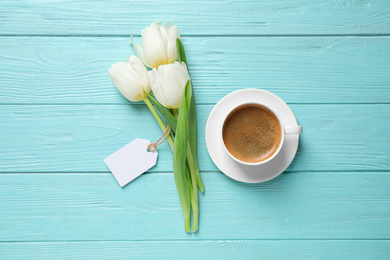 White tulips, coffee and blank tag on light blue wooden table, flat lay with space for text. Good morning