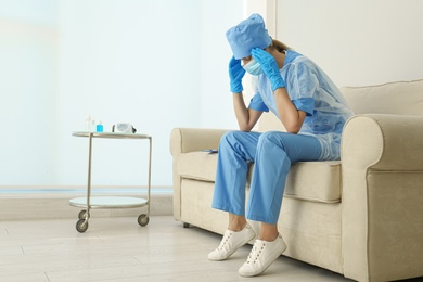 Exhausted doctor sitting on sofa indoors. Stress of health care workers during COVID-19 pandemic
