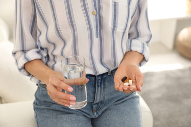Young woman with glass of water and vitamins indoors, closeup