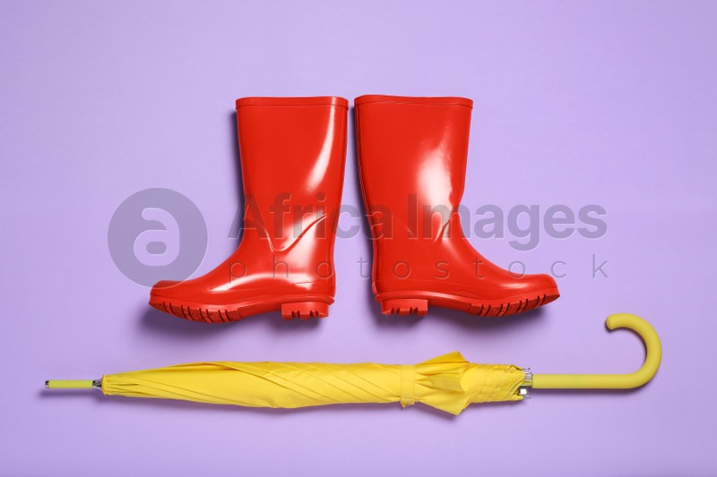Pair of red rubber boots with yellow umbrella on violet background, flat lay