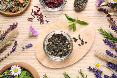 Flat lay composition with healing herbs on wooden table