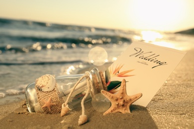 Wedding invitation and glass bottle on sandy beach at sunset