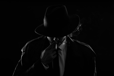 Old fashioned detective smoking cigarette on dark background, black and white effect