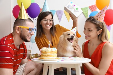 Happy friends celebrating their pet's birthday in decorated room